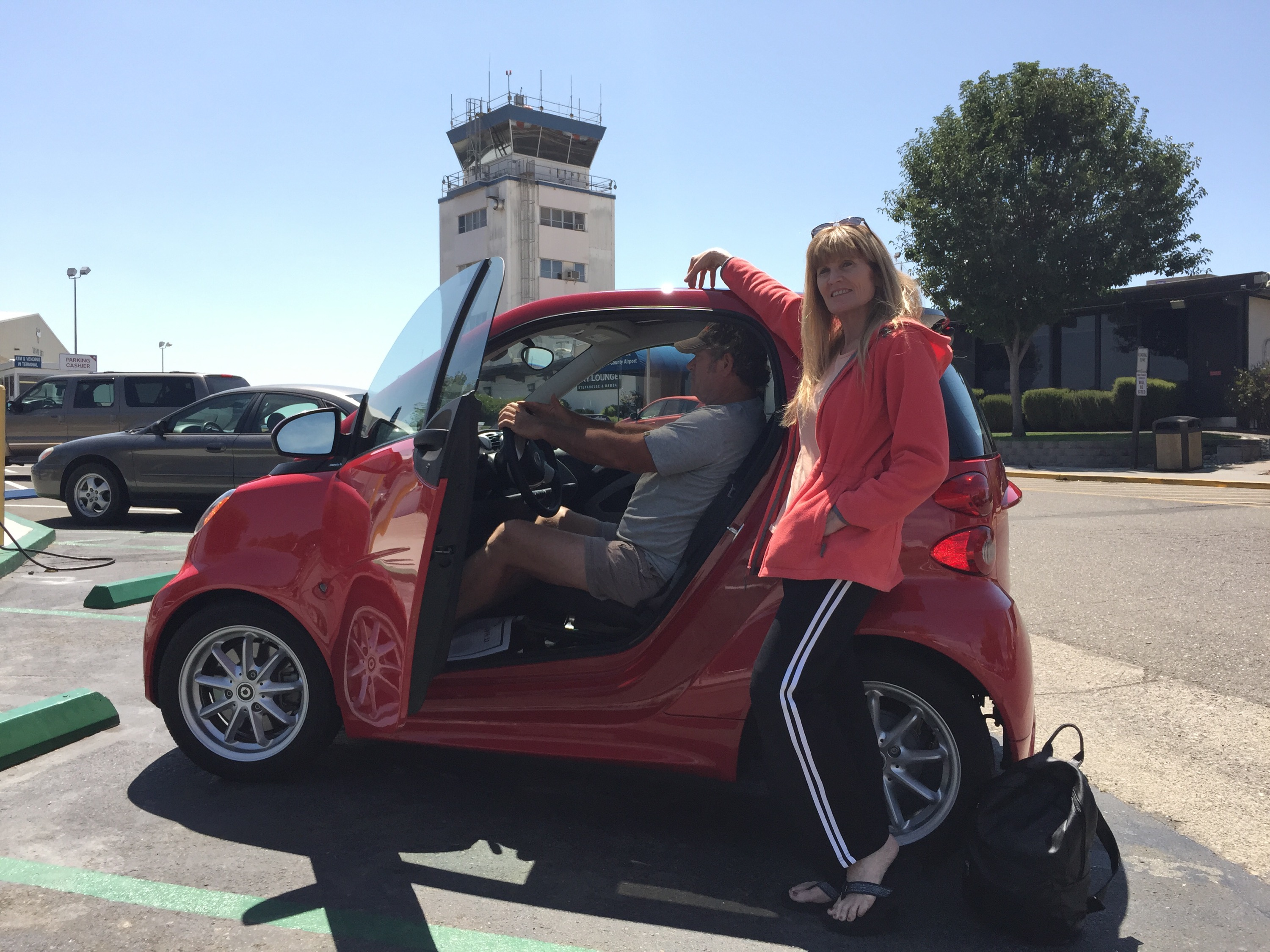Couple with a Smart Car at the Charles M. Schulz - Sonoma County Airport STS